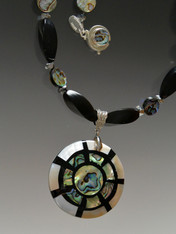"""Make a dramatic statement with this natural black horn swirl, faceted pyrite and abalone pendant necklace. Pendant features mother of pearl, abalone, black horn, and sterling silver in an on-trend geometric pattern. Necklace 19"""" Pendant 2"""""""