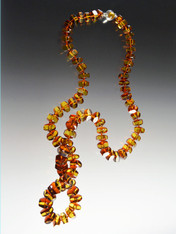 This grade AAA Baltic Amber one of a kind  necklace features hexagon shaped amber beads with rich amber inside and a slight border of darker reddish amber on the edges. The individual beads are linked with hand-knotted double Japanese knots and an amber sterling clasp allows the necklace to be doubled or worn as a single long rope.  33""