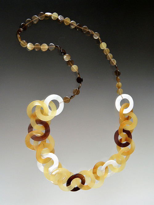 This lightweight on trend necklace features luminous natural makabibi shell,horn, and mother-of-pearl linked circles in tones of amber, tortoise, dark brown and white with smaller natural horn discs around the neck for extra comfort.  22""