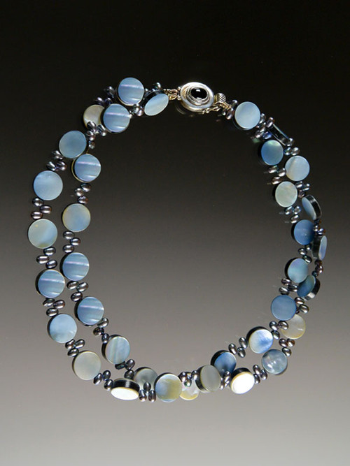 A blue by any other name could be denim, sky, cloud, azure or a host of other tones. Whatever the shade, it's the on-trend color of the season. This double strand iridescent mother-of-pearl coin necklace spaced with peacock navy freshwater pearls is right on trend and perfect for the coming season.  20""