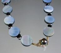 This long iridescent mother-of-pearl coin necklace spaced with peacock navy freshwater pearls is right on trend and perfect for the coming season.  A freshwater pearl sterling clasp lets you wear it single or double for extra versatility. 28""
