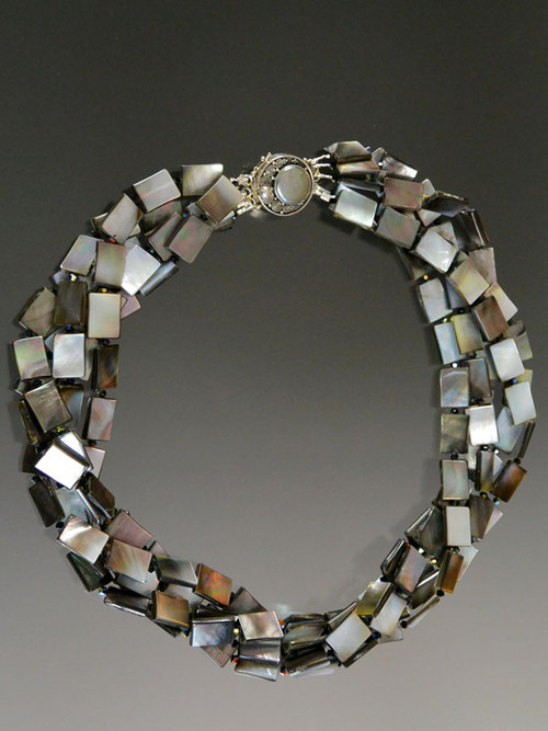 This fabulous multi strand torsade of faceted mother-of-pearl tiles spaced with tiny jet Swarovski crystals shoots of sparks of black, white, bronze, and many other tones, held with a custom sterling silver mabe pearl clasp. Wear it for any occasion - understated yet super elegant. 20""
