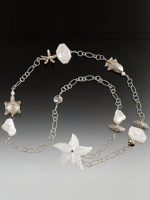 This one of a kind sterling silver chain necklace features mother-of-pearl faceted slices and sterling silver starfish, seashells, and other marine creatures collected over many years.  28""