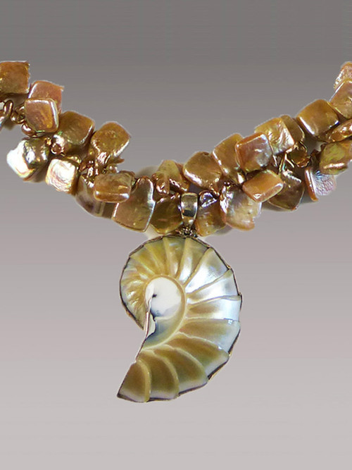 "A stunning pale champagne perfectly formed and naturally outlined nautilus shell anchors a necklace of unusual and highly dimensional (suggesting a double strand) square champagne pearls with a fabulous lustre. They can go from day to night without missing a beat.  18"" Nautilus Shell 2"""
