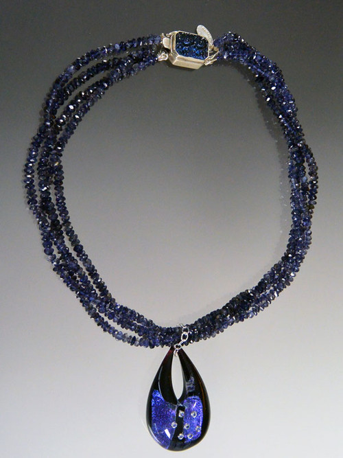 "Blue is a big color trend this season and this dazzling necklace has it all - three strands of grade AAA Iolite (a member of the sapphire family) rondels with a custom sterling iolite clasp and a one of a kind authentic Venetian glass pendant in the shape of a teardrop featuring sterling silver over deep blue Murano Glass with sparkling cubic zirconia near the surface.  The entire teardrop is encased in clear Murano Glass giving it a magnified effect. Totally stunning in person with great depth and flashes of color. 22"" Pendant 1-1/2"""