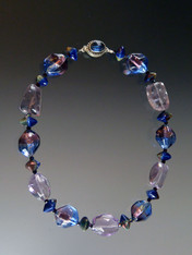 This magnificent statement necklace features Grade AAA lilac amethyst smooth clear pebbles, limited edition tri-color blue, purple, sterling silver Venetian sasso three dimension beads*, Greek ceramic midnight oil oxyhedron beads, swarovski crystals, and a vintage sterling blue clasp. 17-1/2  ONLY TWO!