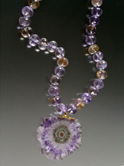 A gorgeous amethyst banded stalactite* pendant hangs from a collar of faceted grade AAA ametrine rondels.
