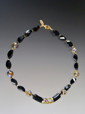 "This necklace  features a limited edition 60mm Venetian glass focal curved ""Klimt"" tube of black Murano Glass with a center exterior section of 24K gold with small bits of embedded millefiori mosaic resembling a Klimt painting. The rest of the necklace features onyx swirls, round Klimt mosaics, and 24K Swarovski plated beads.  18"""