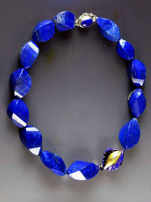 """Fine lapis is becoming increasingly rare and expensive.  This one-of-a-kind statement necklace features grade AAA lapis faceted swirls with a 24K blue edged Venetian glass focal highlight and a lapis sterling clasp. 18"""""""