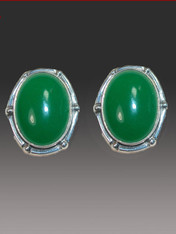 "Green is THE color this season and these striking Amy Kahn Russell earrings will go with everything in your wardrobe. They feature bright green onyx cabochons bezel set in an intricate sterling silver frame. 1"" x 3/4"" Clips   Convert to posts for $15."