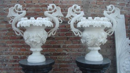 VERY ORNATE, OVER THE TOP, HAND CARVED MARBLE URNS ON BLACK PEDESTALS