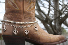 "Boot Candy is the best thing to happen to your boots since you broke them in... This item contains Natural Howlite, White beads and sparkling clear Czech crystals.  The accent silver plated chain holds 4 Natural Howlite, White Peace charms.  Adjustable to fit your cowboy boots, your fashion boots and your winter boots, too! Length:  14.25"" to 15.75"" adjustable. Made in Texas, USA."