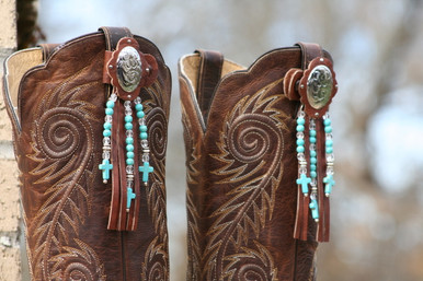 100% real leather.  Chocolate leather, Silver Plated Oval Conchos with fringe and Turquoise beads.
