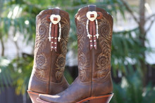 Boot Candy Boot Toppers Attach through your Boot Pull Straps.   This pair is made with Chocolate Leather, Slotted Silver Heart Conchos, White beads and Crosses and Fringe.