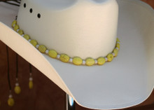"CTL Hat Bands are made of Colored Gem Stones and Leather Lace.  This CTL Hat Band contains Yellow Ovals with White Round Beads.   The Brown leather Lace is accented with the same Colored Stones and ties in the back of the hat.  The Gem Stone Strand measures 20"" and the Leather Lace Measures 14"" and will drape down the back if your hat."