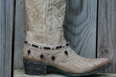 "Boot Candy is the best thing to happen to your boots since you broke them in... This item contains Natural Howlite, dyed Black beads and sparkling clear Czech crystals.  The accent silver plated chain holds 4 Natural Howlite, dyed Black Cross charms.  Adjustable to fit your cowboy boots, your fashion boots and your winter boots, too! Length:  14.25"" to 15.75"" adjustable. Made in Texas, USA."