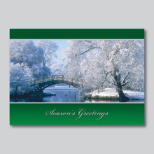 Winter bridge with white snowing trees and silver simulated Season's greetings.