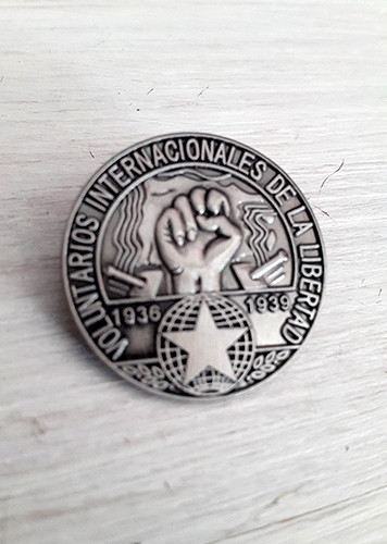 Reproduction of original International Brigade blouson badge with brooch fixing.  3D badge has map of Spain, cannons, clenched fist, star and the text 'Voluntarios Internacionales de la Libertad'.