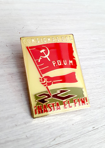 A quality enamel badge reproducing a POUM poster from the Spanish Civil War.  Original text on poster read 'Consignas del POUM. !Hasta El Fin!' With image of arm stabbing a red POUM flag into a swastika.
