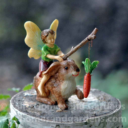 Little Boy Fairy Motivating a Rabbit with Stick and Carrot