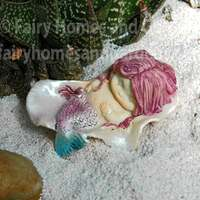 Little Mermaid Sleeping in a Seashell on White Beach Sand