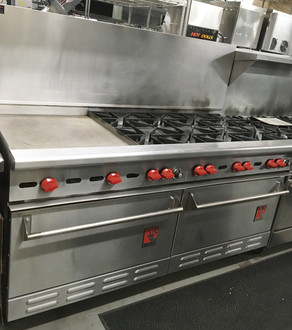 """USED Wolf 68"""" Range. 8 Open Burners & 22"""" Griddle, 2 Standard Ovens, Natural Gas, Front, sides, back riser and high shelf finished in stainless steel. Stainless steel bullnose, front manifold cover and 6"""" adjustable legs. 26,000 BTU/hr. open burners with lift-off heads. Flashtube pilot ignition system for automatic burner lighting, Full width pull out crumb tray. 30,000 BTU/hr. standard oven measures 29""""w x 22""""d x 13""""h. Thermostat adjusts from 250 to 500 F. One oven rack and four rack positions, 67 1/4""""w x 32 3ƒ?4""""d x 57 1/2""""h on 6"""" adjustable legs. 37"""" working height."""