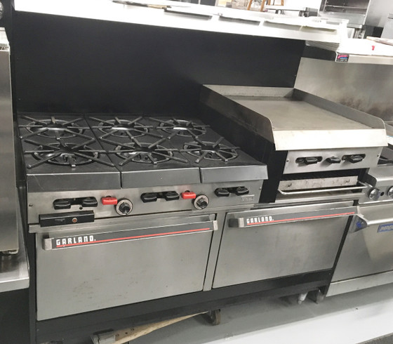 "GARLAND 60"" RANGE.  6 BURNERS, 24"" RAISED GRIDDLE/ BROILER.  1 CONVECTION OVEN (LEFT), 1 STANDARD OVEN (RIGHT)."
