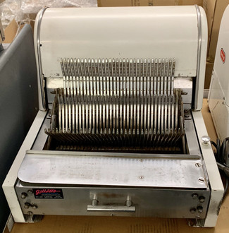 "Bread Slicer, countertop, 7/16"" slice thickness, 1-speed, alloy carbon steel blades, stainless steel bagging trough, removable scrap pan, on/off toggle switch with safety guard, white polyester powder coat exterior, 1/3 HP, 115v/60/1-ph, 6.2 amps, 6' cord & plug, ETL, NSF"