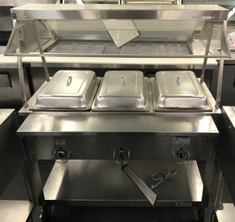 USED DUKE EP303M ELECTRIC 3 WELL STEAM TABLE. 120v. COMES WITH ATTACHED SNEEZE GAURD, WAITER PANS AND COVERS.