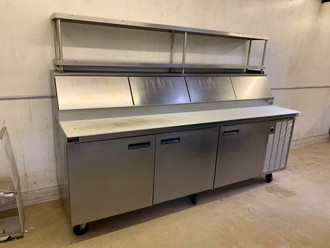 "USED DELFIELD Refrigerated Pizza Table, three-section, 99"" W, 25.87 cubic feet, (12) 1/3 pan capacity, (3) shelves, (3) 27"" doors, 18 gauge stainless steel top, refrigerated pan rail, stainless steel ends, 6"" casters, side-mounted refrigeration system, (2) 1/5 hp, cUL, UL, NSF 7"