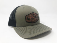 Olive green cap with black mesh, leather patch.