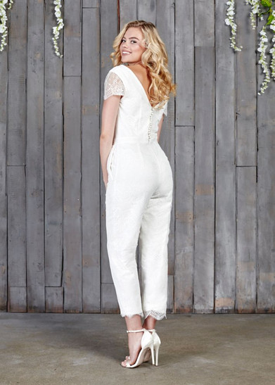 The all-new Lowry epitomises the modern day bride. The new design has a classic and flattering cigarette cut trouser leg. The bridal lace comes all the way from Australia and boasts a contemporary, fan design while giving a pretty, vintage vibe. Gentle V-neck at the front and back. The capped sleeves and trouser leg are both finished with a scalloped edge. 12 bridal covered buttons run down the back. Handmade in London