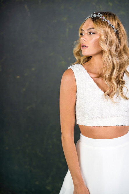 This super cool beaded top adds a touch of glamour to any bridal look. Both the front and back boast a flattering V shape. The simple boxy style is complemented with heavy embellishment striking the perfect balance between simplicity and detail.