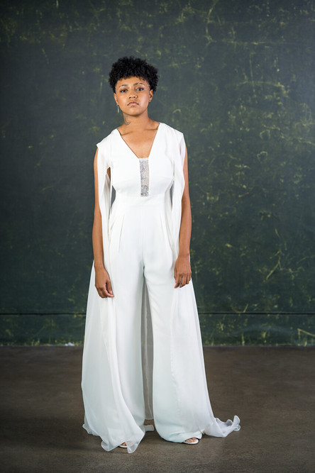 A structured bridal jumpsuit with a cinched-in waist and wide trouser legs. The cut-out sides and 80s themed shoulder shape will give any wedding day a touch of attitude.