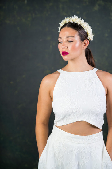 This contemporary bridal top has a lace frontage and illusion lace back. The on-trend curve at the front creates a subtle flash of tummy. Simple straps rest on the flattering collar bone area creating a modern shape. The Stevenson top features here with the Stevenson skirt.