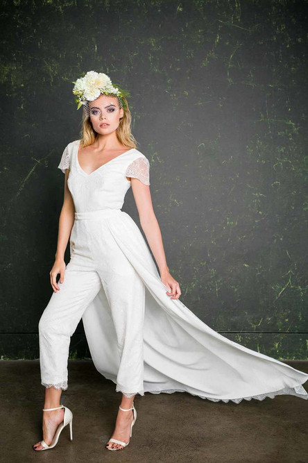 The Lowry epitomises the modern day bride. This design has a classic and flattering cigarette cut trouser leg. This beautiful bridal jumpsuit is made entirely of lace which comes all the way from Australia and boasts a contemporary, fan design while giving a pretty, vintage vibe. The capped sleeves and trouser hem are both finished with a scalloped edge.