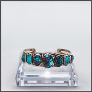 7 bezel set turquoise stones on sterling silver cuff.