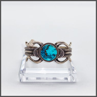 Round oval Royston turquoise center stone, sterling silver cuff. Front View-This piece was created by W. Begay.