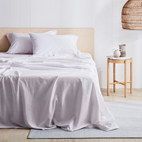 Blush White Sheet Set on wooden bed frame, next to wooden side table and light shade