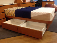 Twin Size Platform bed shown with 2 drawers left facing. Drawers can face left or right. Shown in Wild Cherry but available in dozens of finishes from Wilsonart, Formica, Pionite & Nevamar. Available in Full, Queen & King Sizes also. Solid platform deck requires mattress only. Shown with optional storage headboard. Get the mattress at The Bedroom Source. It will be delivered same time as the bed with no extra delivery charge. Special financing available*